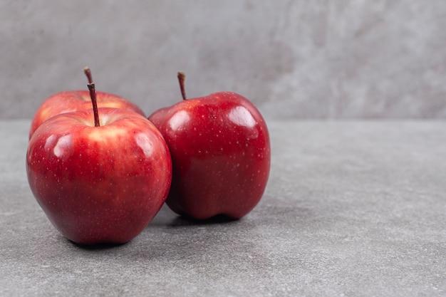 Trois pommes rouges sur une surface en marbre