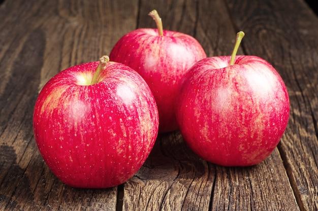 Trois pommes rouges sur table en bois