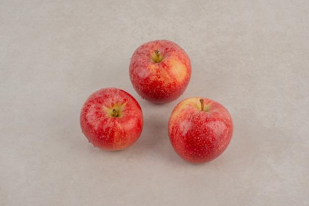 Trois pommes rouges sur table en marbre.