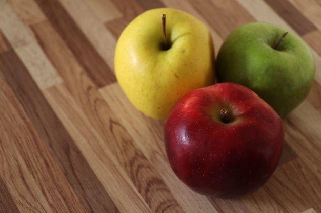 Trois pommes sur une table en bois pomme rouge pomme jaune et pomme verte