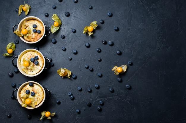Trois portions de pudding de riz anglais classique. myrtilles et physalis.