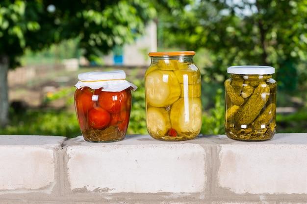 Trois pots de légumes fraîchement conservés sur un mur de briques - pot de tomates marinées, d'oignons et de concombres devant le jardin