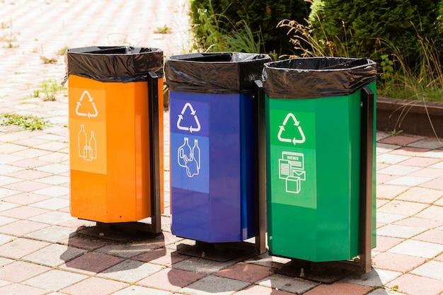 Trois poubelles colorées dans un parc à côté d'un sentier.