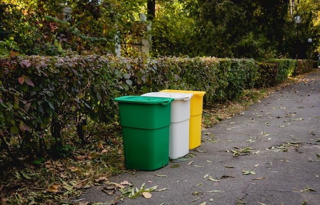 Trois poubelles de couleurs différentes pour les déchets triés. à l'extérieur dans la zone du parc. concept zéro déchet