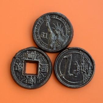 Trois produits au chocolat sous la forme de pièces en euros, aux états-unis et au japon reposent sur un fond en plastique orange.