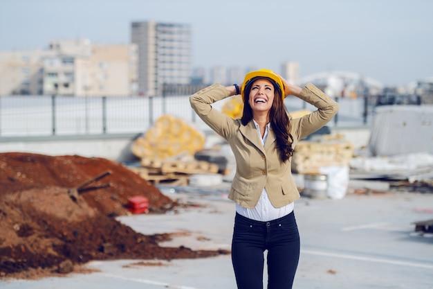 Trois quarts de longueur de l'architecte femme caucasienne heureuse en veste beige et avec un casque de protection sur la tête et en levant en se tenant debout sur le chantier de construction.
