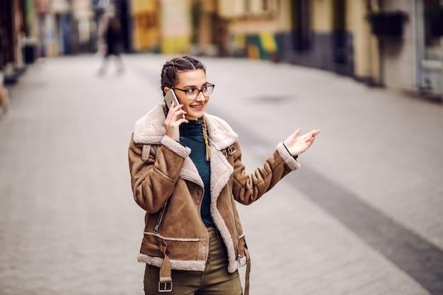 Trois quarts de longueur de souriante jolie jeune fille debout dans la rue et parler au téléphone.