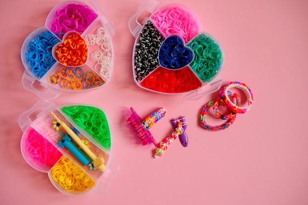 Trois récipients en forme de cœur remplis d'élastiques colorés pour tisser des bracelets