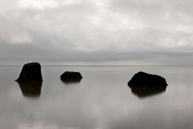 Trois roches solitaires s'élevant de l'océan calme à l'horizon par temps nuageux