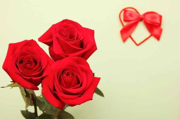Trois roses rouges et l'arc rouge sur le coeur