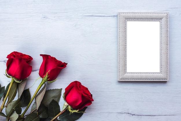 Trois roses rouges, sur une table en bois avec cadre photo, espace copie