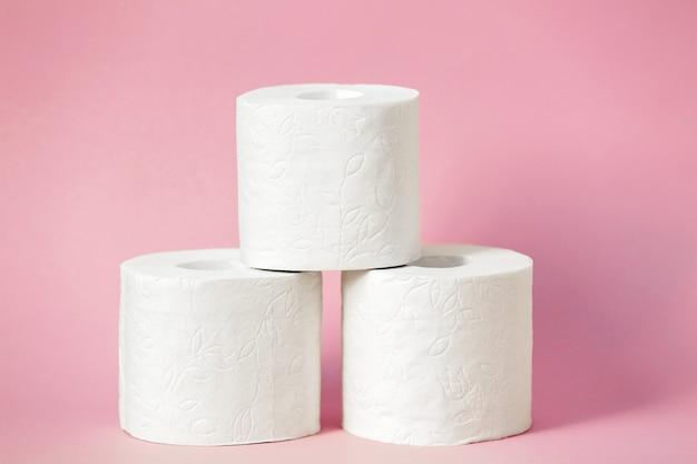 Trois rouleaux de papier toilette blanc se tiennent sur un fond rose