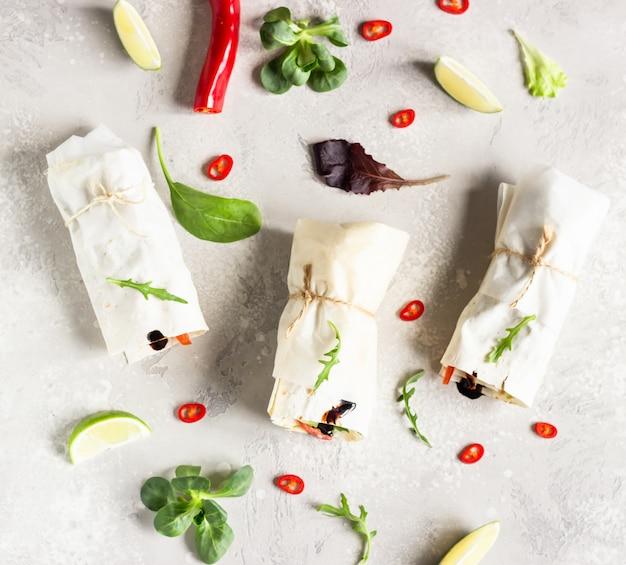Trois roulés de tortillas végétaliens, sandwichs roulés aux légumes, mélange de salade verte, citron vert et piment