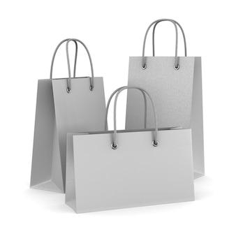 Trois sacs-cadeaux en papier sur blanc. illustration 3d isolée