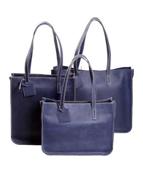 Trois sacs à main de luxe pour femmes bleu isolé sur blanc. macrophotographie.