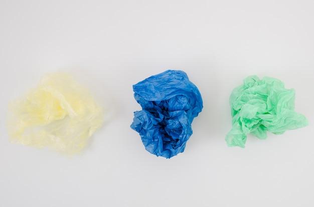 Trois sacs de plastique froissé dans une rangée isolée sur fond blanc
