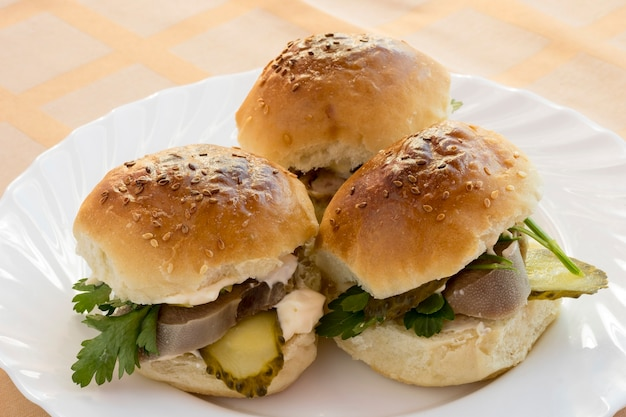 Trois sandwich avec langue de boeuf et cornichons.