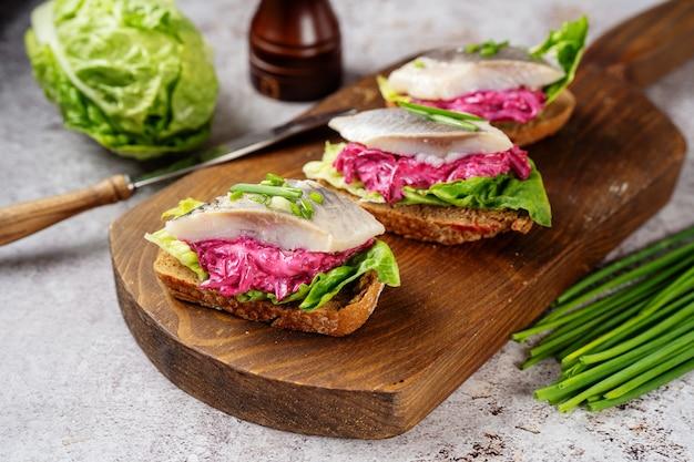 Trois sandwichs au hareng avec de la betterave et des feuilles de salade verte sur planche de bois