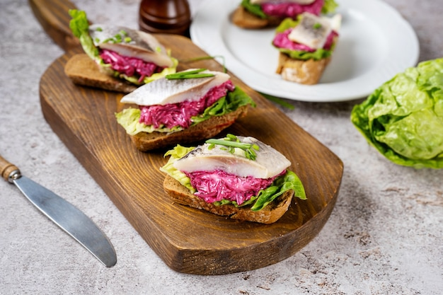 Trois sandwichs avec hareng salé, betterave et salade verte