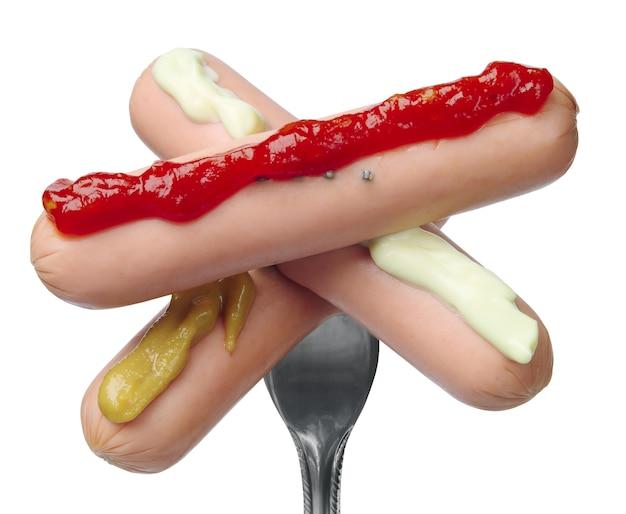 Trois saucisses sur une fourchette avec une sauce différente, d'isolement sur le blanc