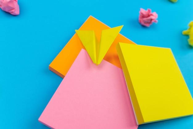 Trois séries d'autocollants en jaune, rose, orange avec une figure d'un autocollant jaune en forme d'avion. bleu . autocollants froissés. fermer. ensembles pour les notes.