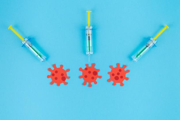 Trois seringues piquant trois virus rouges découpés dans du papier.