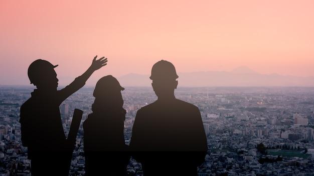 Trois silhouette de l'équipe d'ingénieurs regardant le développement de tokyo