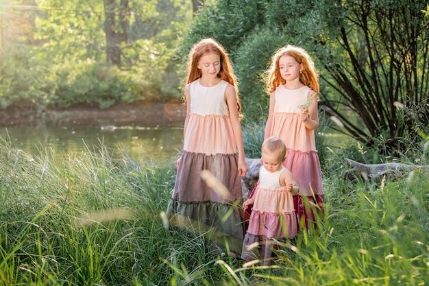 Trois sœurs rousses vêtues de longues robes en lin se reposent sur le lac du parc par une journée d'été ensoleillée.