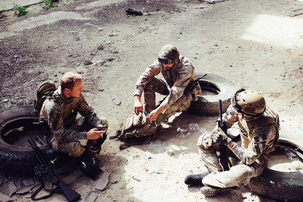 Trois soldats sont assis sur des pneus et se reposent. ils se sont bien battus. les hommes veulent garder leur force pour le prochain combat. l'un d'eux tient des fils pendant que l'autre ouvre le sac.
