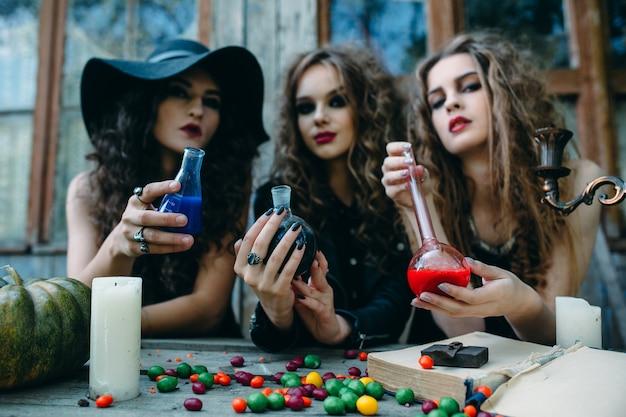 Trois sorcières sont assises à table et préparent la potion à la veille d'halloween