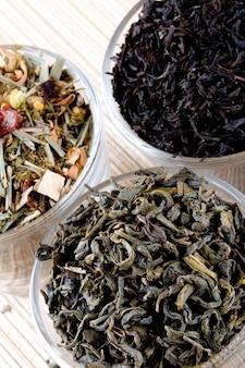 Trois sortes de thé sec dans des verres closeup sur fond de paille