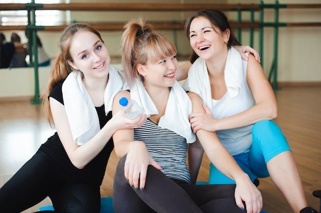 Trois sportives gaies riant et s'amusant après l'entraînement dans la salle de gym.