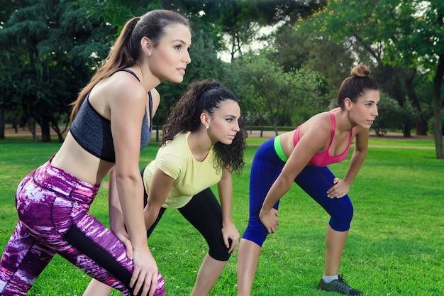 Trois sportives prêtes à courir dans le parc