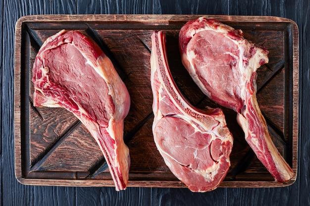Trois steaks de boeuf tomahawk cru vieilli à sec sur une vieille planche à découper en bois grossier, gros plan, mise à plat, vue d'en haut