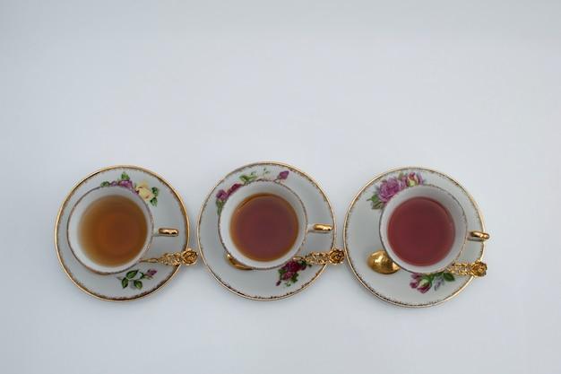 Trois style classique de tasses à thé blanc et or avec différents types de thés