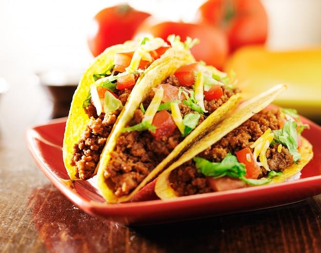 Trois tacos de bœuf avec fromage, laitue et tomates