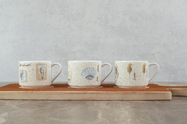 Trois tasses de café sur planche de bois.