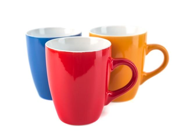 Trois tasses en céramique de couleur sur fond blanc.