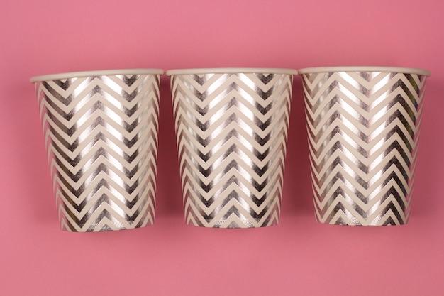 Trois tasses de papier fond rose pastel vue de dessus