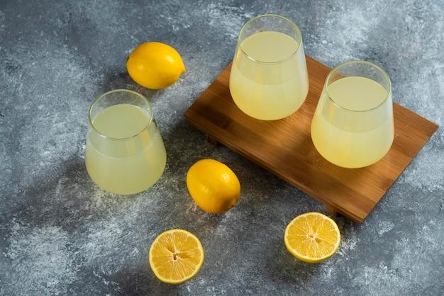 Trois tasses en verre avec du jus de citron frais sur planche de bois.
