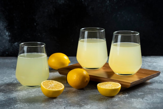 Trois tasses en verre avec du jus de citron sur planche de bois.