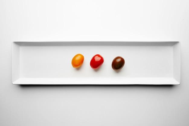 Trois tomates cerises différentes isolées au centre de la plaque blanche, vue du dessus, jaune, rouge et noir