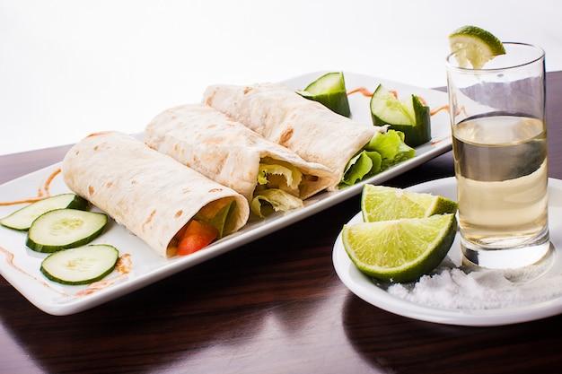 Trois tortillas mexicaines enveloppées de tequila, de citron et de sel sur table en bois, contre une surface blanche