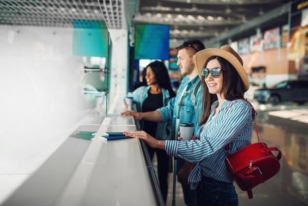 Trois touristes avec des bagages passent le contrôle des passeports à l'aéroport. passagers avec bagages dans l'aérogare, bon voyage, voyage d'été