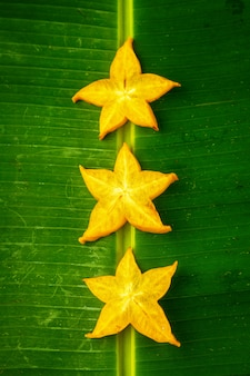 Trois tranches de carambole de fruit étoile jaune mûr ou pomme étoile (carambole) sur feuille de bananier vert, composition verticale