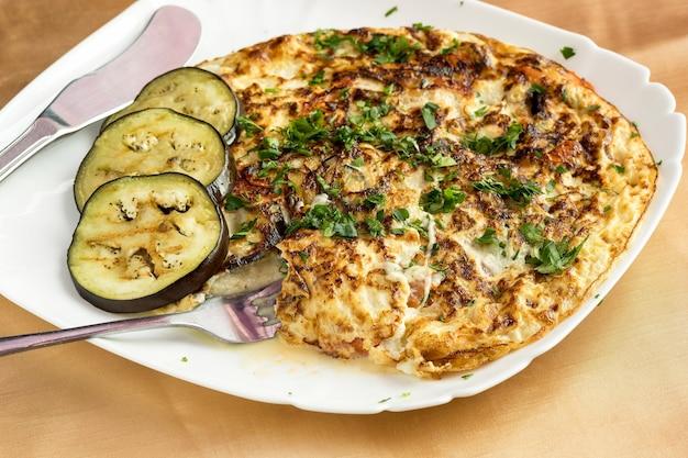 Trois tranches d'omelette aux aubergines et aux légumes.