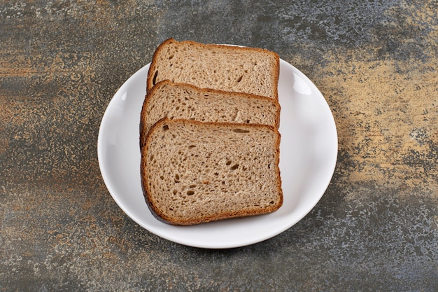 Trois tranches de pain noir sur plaque blanche