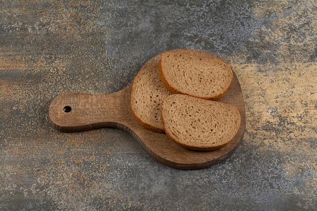 Trois tranches de pain sur planche de bois.