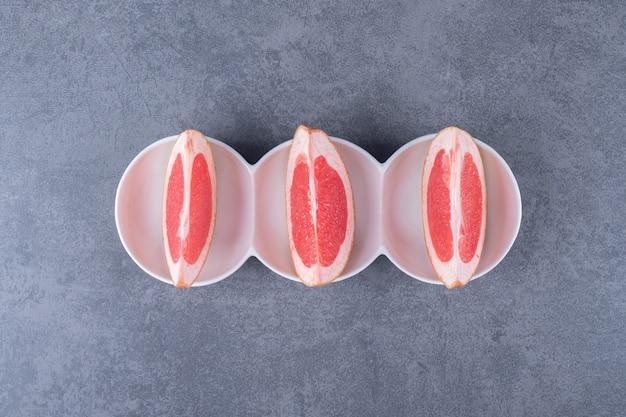 Trois tranches de pamplemousse sur fond gris.