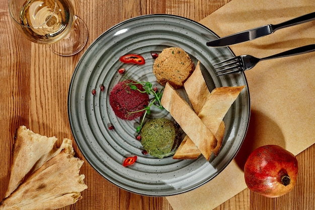 Trois types d'apéritif géorgien traditionnel pkhali, noix moulues aux épinards, betteraves rouges et haricots blancs servis avec grenade, shotis puri frais et verre de vin. vue de dessus sur fond de bois